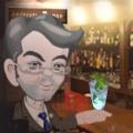 IATRISM BAR のカウンターでカクテルを飲む背広姿のMr. ヤスのヒゲが夜になり濃くなっている情景